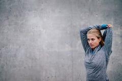 Corridore femminile che allunga armi dopo una sessione corrente fotografie stock