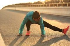 corridore femminile che allunga le sue gambe sulla strada di alba Immagine Stock