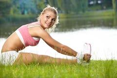 corridore femminile che allunga prima del suo allenamento Fotografia Stock