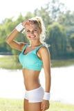 Corridore femminile che allunga prima del suo allenamento Fotografie Stock