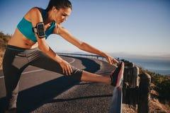 Corridore femminile che allunga prima dell'correre Fotografia Stock Libera da Diritti