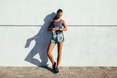Corridore femminile che controlla progresso di forma fisica Immagini Stock