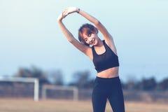 Corridore femminile che fa allungando esercizio, preparante per la mattina w Fotografia Stock