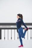 Corridore femminile che fa esercizio di flessibilità per le gambe prima del funzionamento alla passeggiata di inverno della neve, Fotografia Stock