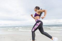Corridore femminile che pareggia durante l'allenamento all'aperto sulla spiaggia Fotografie Stock