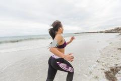 Corridore femminile che pareggia durante l'allenamento all'aperto sulla spiaggia Immagine Stock Libera da Diritti