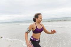 Corridore femminile che pareggia durante l'allenamento all'aperto sulla spiaggia Fotografia Stock