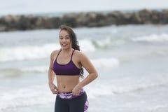 Corridore femminile che pareggia durante l'allenamento all'aperto sulla spiaggia Immagini Stock