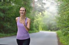 Corridore femminile che pareggia durante l'allenamento all'aperto in un parco Immagini Stock