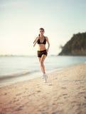 Corridore femminile che pareggia durante l'allenamento esterno sulla spiaggia Immagine Stock