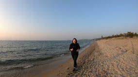 Corridore femminile che pareggia sulla spiaggia sabbiosa al tramonto stock footage