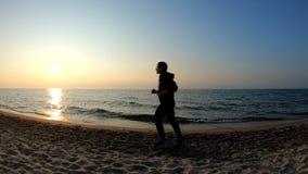Corridore femminile che pareggia sulla spiaggia sabbiosa al tramonto archivi video