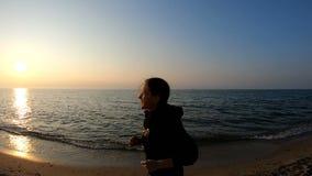 Corridore femminile che pareggia sulla spiaggia sabbiosa al tramonto video d archivio