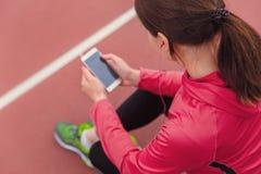Corridore femminile che per mezzo del telefono cellulare ed ascoltando la musica mentre riposando dopo avere pareggiato immagini stock