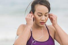 Corridore femminile che prepara per l'allenamento all'aperto sulla regolazione della spiaggia Immagine Stock