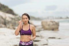 Corridore femminile che prepara per l'allenamento all'aperto sulle cuffie di messa in opera della spiaggia Fotografie Stock Libere da Diritti