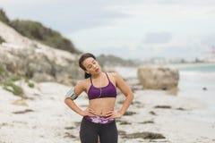 Corridore femminile che prepara per l'allenamento all'aperto sulle cuffie di messa in opera della spiaggia Fotografia Stock