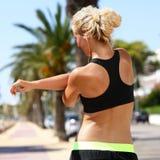 Corridore femminile di sport che allunga armi prima dell'correre Fotografie Stock