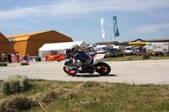 Corridore femminile solo della motocicletta alla svolta a sinistra sulla pista Fotografie Stock Libere da Diritti
