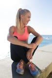 Corridore femminile sorridente che gode del suo resto dopo l'esercizio fisico attivo all'aperto Fotografia Stock