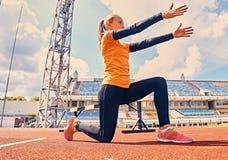 Corridore femminile sportivo biondo alla posizione di inizio rapido Fotografia Stock Libera da Diritti