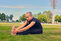 Corridore femminile sportivo biondo alla posizione di inizio rapido Fotografie Stock