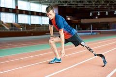 Corridore handicappato che allunga nello stadio fotografia stock