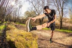 Corridore maschio che allunga all'aperto Fotografia Stock Libera da Diritti