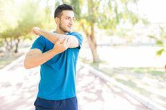 Corridore maschio che allunga braccio prima dell'allenamento in parco immagine stock libera da diritti