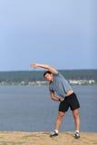 Corridore maschio che fa allungando esercizio, preparante per l'allenamento di mattina nel parco Fotografia Stock