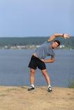 Corridore maschio che fa allungando esercizio, preparante per l'allenamento di mattina nel parco Immagine Stock