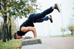 Corridore maschio che fa esercizio, allenamento nel parco di caduta Spinga aumenta con il banco Fotografia Stock