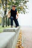 Corridore maschio che fa esercizio, allenamento nel parco di caduta Spinga aumenta con il banco Immagini Stock