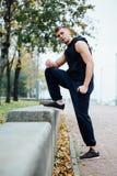 Corridore maschio che fa esercizio, allenamento nel parco di caduta Spinga aumenta con il banco Immagine Stock