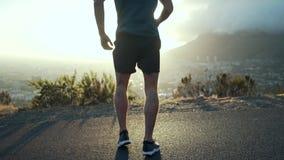 Corridore maschio di forma fisica che allunga le gambe prima dell'correre archivi video
