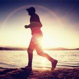 Corridore nei raggi di Sun sulla spiaggia Sportivo in berretto da baseball, pareggiante durante l'alba sopra il mare Immagini Stock Libere da Diritti