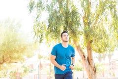 Corridore nell'addestramento degli abiti sportivi nel parco immagine stock libera da diritti