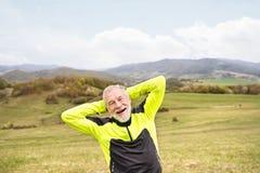 Corridore senior attivo fuori sulle colline verdi che fanno allungamento Immagini Stock Libere da Diritti