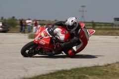 Corridore solo della motocicletta alla svolta a sinistra sulla pista Fotografie Stock