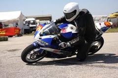 Corridore solo della motocicletta alla svolta a sinistra sulla pista Fotografie Stock Libere da Diritti