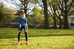 Corridore stanco della donna che prende un resto dopo avere corso duro Fotografie Stock