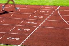 Corridore su una pista corrente che finisce una corsa in primo luogo Fotografia Stock