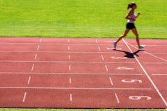 Corridore su una pista corrente che finisce una corsa in primo luogo Immagine Stock Libera da Diritti
