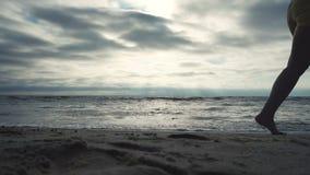 Corridore sul litorale contro il tramonto stock footage