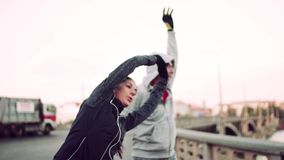 Corridori adatti di una coppia che fanno allungamento all'aperto sul ponte nella città di Praga archivi video