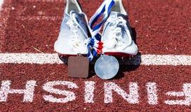 Corridori che corrono le punte con le medaglie all'arrivo fotografia stock