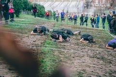 Corridori che strisciano sotto il filo spinato in una prova della corsa di ostacolo estrema Fotografia Stock
