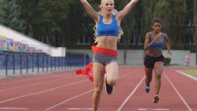 Corridori maratona femminili che attraversano traguardo sull'arena di sport professionali archivi video