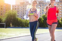 Corridori sulla pista dello stadio Allenamento di forma fisica di estate delle donne Fotografia Stock