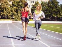 Corridori sulla pista dello stadio Allenamento di forma fisica di estate delle donne Fotografie Stock Libere da Diritti